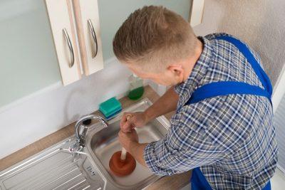 Plombier débouche un évier avec une ventouse
