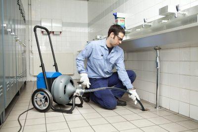 Plombier débouche une canalisation ave un furet électrique