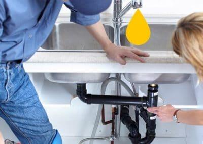 Plombier pose un évier de cuisine et raccorde les tuyaux