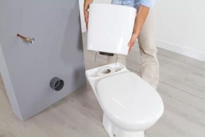 plombier assure le placement du WC