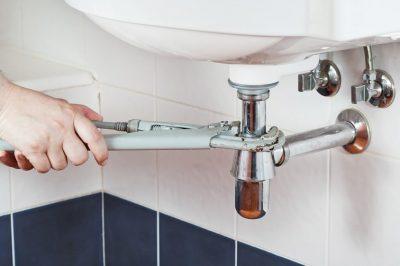 plombier répare la conduite eau du lzvabo
