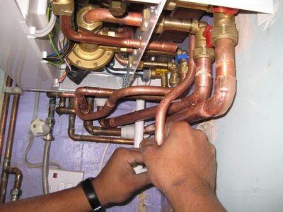 Le chauffagiste vérifie la jointure des tuyaux de la chaudière